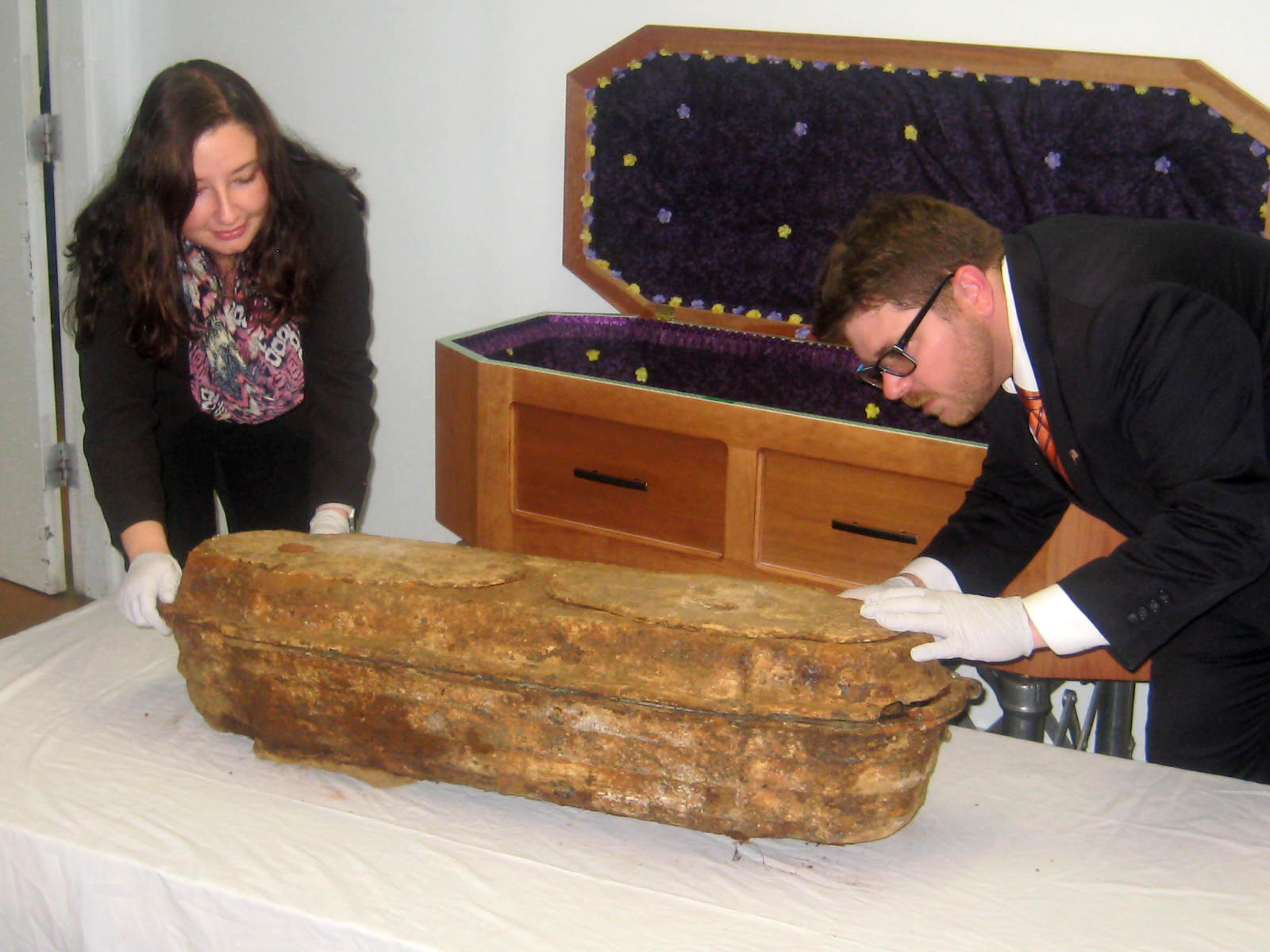 Santa Cruz Memorial apprentice embalmer Megan Mackenzie and funeral director Lincoln Krassow examine and place the girl's original casket into her new casket, which was specially built to accommodate the original burial container.