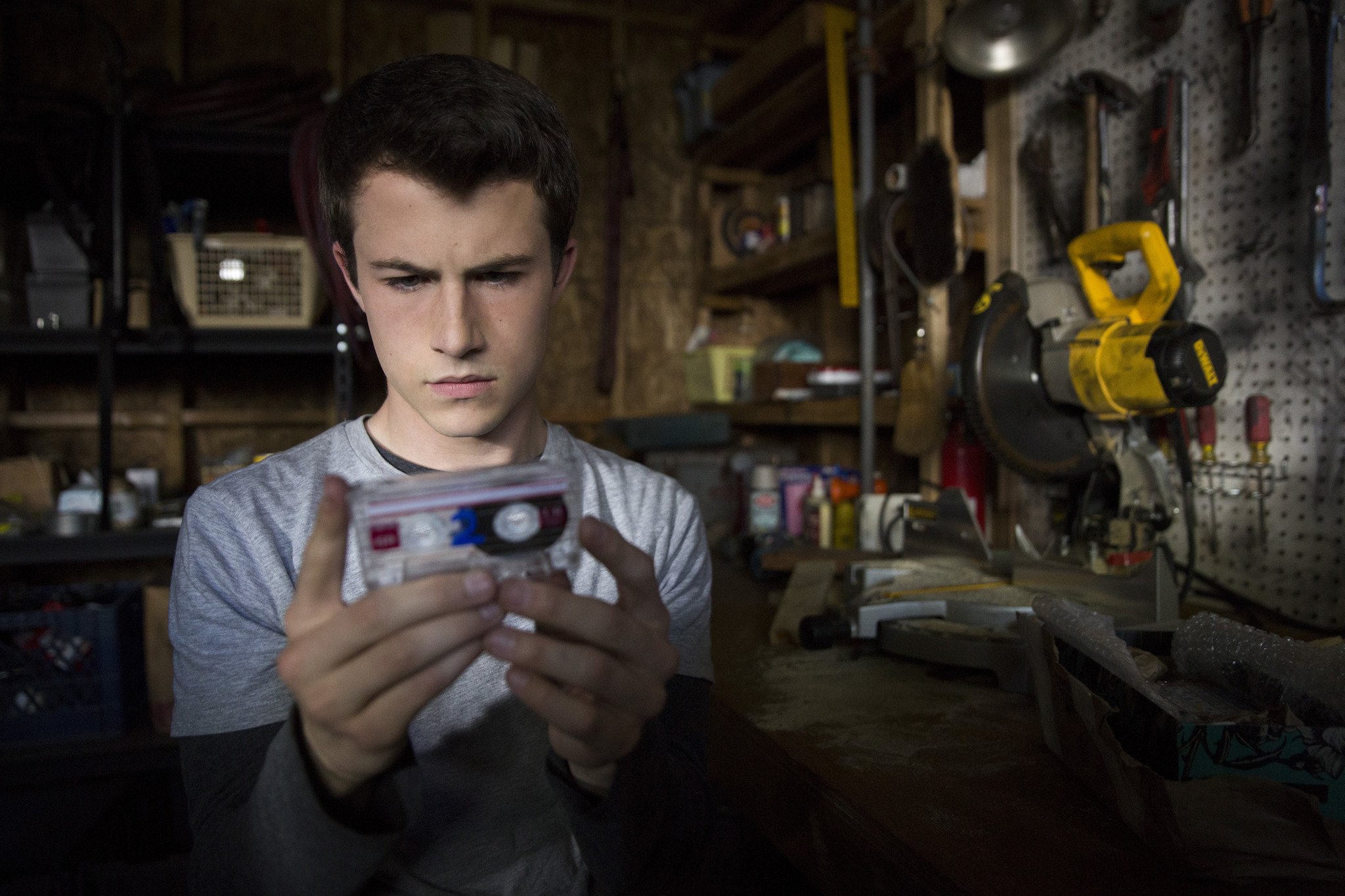 "Dylan Minnette (playing Clay Jensen) listen to the tapes of deceased character Hannah Baker on ""13 Reasons Why."""