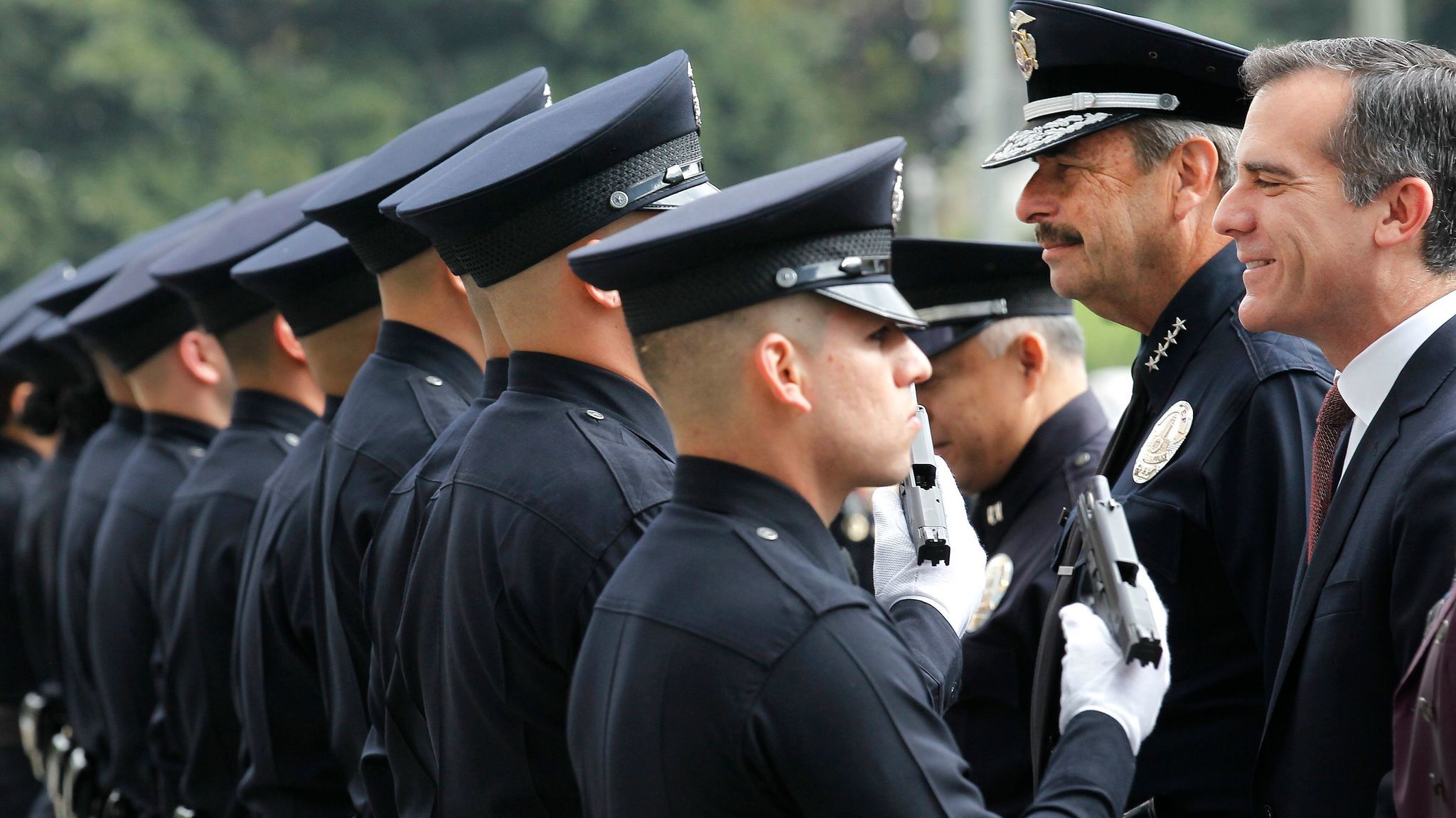 Police Chief Charlie Beck, second from right, and Mayor Eric Garcetti, right. inspect a new group of LAPD officers at a 2015 graduation ceremony.