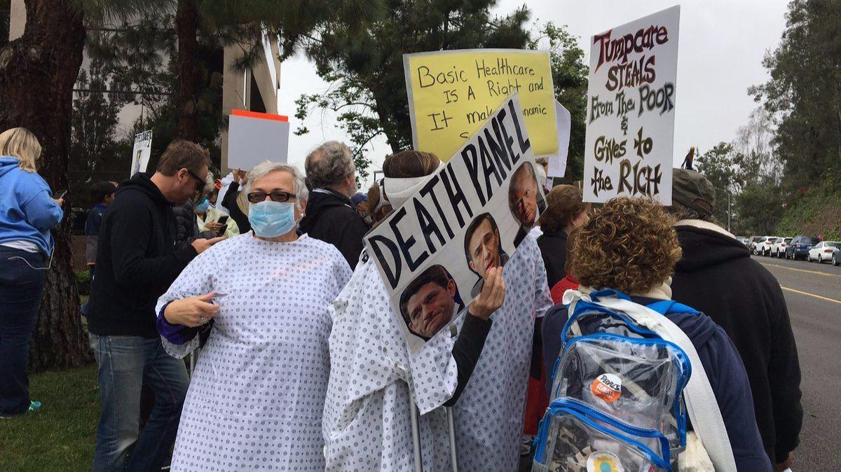 Protesters don hospital gowns and surgical masks outside Rep. Darrell Issa's Vista office to protest