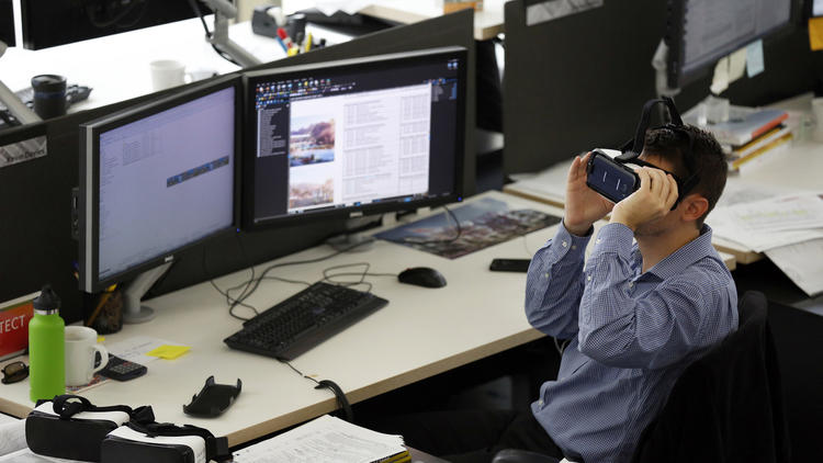 Architect Kevin Davies works with virtual reality goggles at his work station to get a better idea o