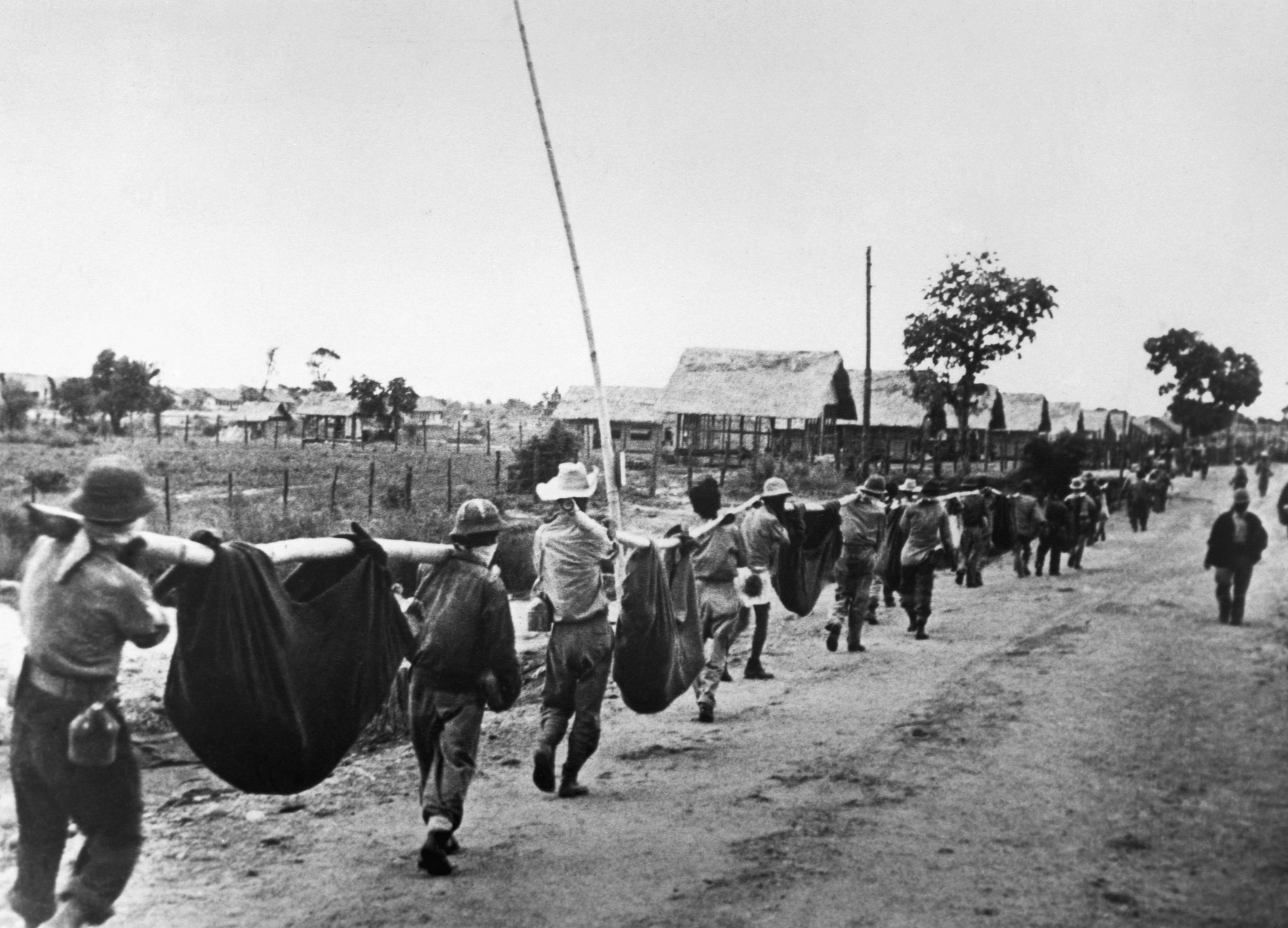 American prisoners of war use improvised litters to carry casualties in April 1942 as they near a Japanese POW camp about 65 miles inland from the Bataan Peninsula.