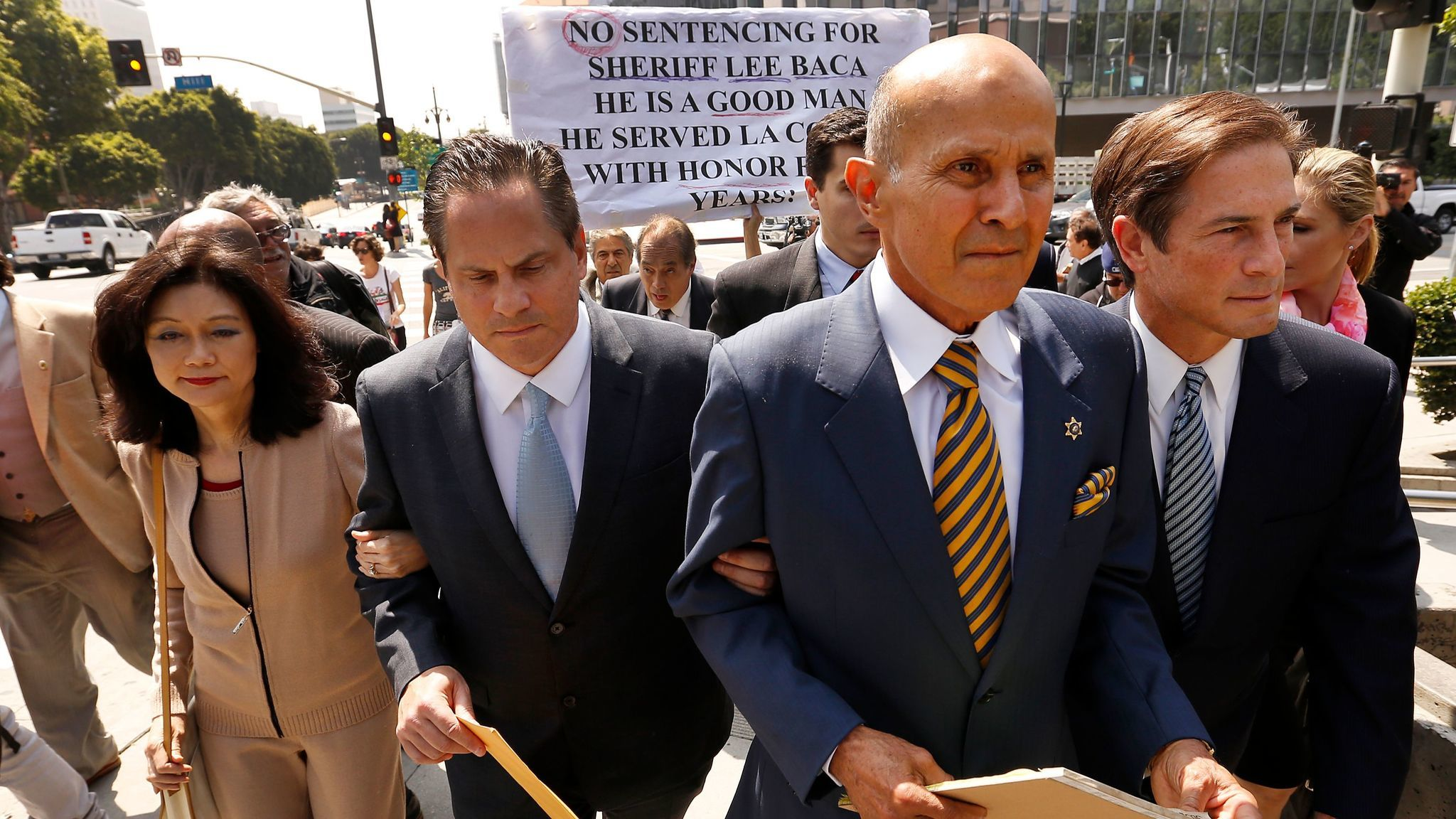 Former Los Angeles County Sheriff Lee Baca, second from right, leaves a downtown courthouse Friday after being sentenced to three years in prison for his role in a 2011 plan to obstruct an FBI investigation into county jails.
