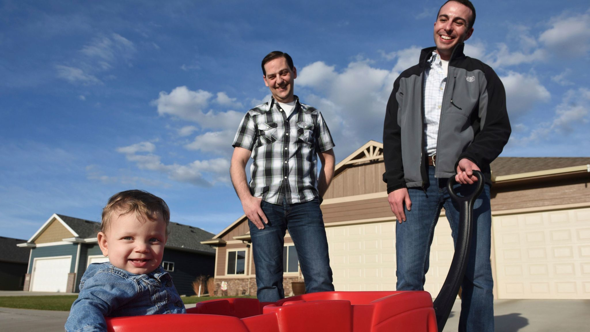 Greg Roling, center, and Larry Sandal take a stroll with their 9-month-old adopted daughter, Emmersyn Julia Roling, in Sioux Falls, S.D., in April 2017.