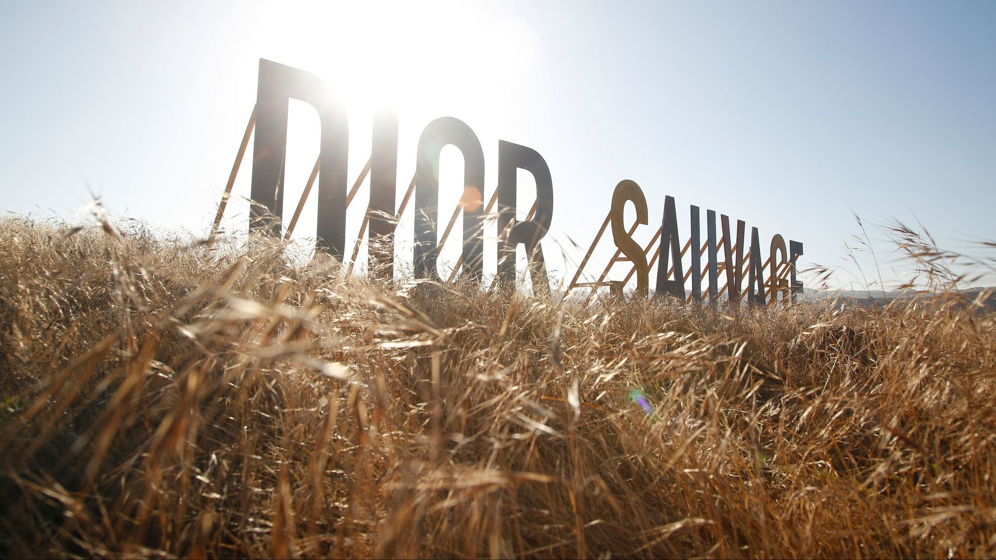 Letters displaying the name of the collection, Dior Sauvage, stand on a Calabasas hillside, one of many signs to mark the occasion, Dior's cruise collection presentation.