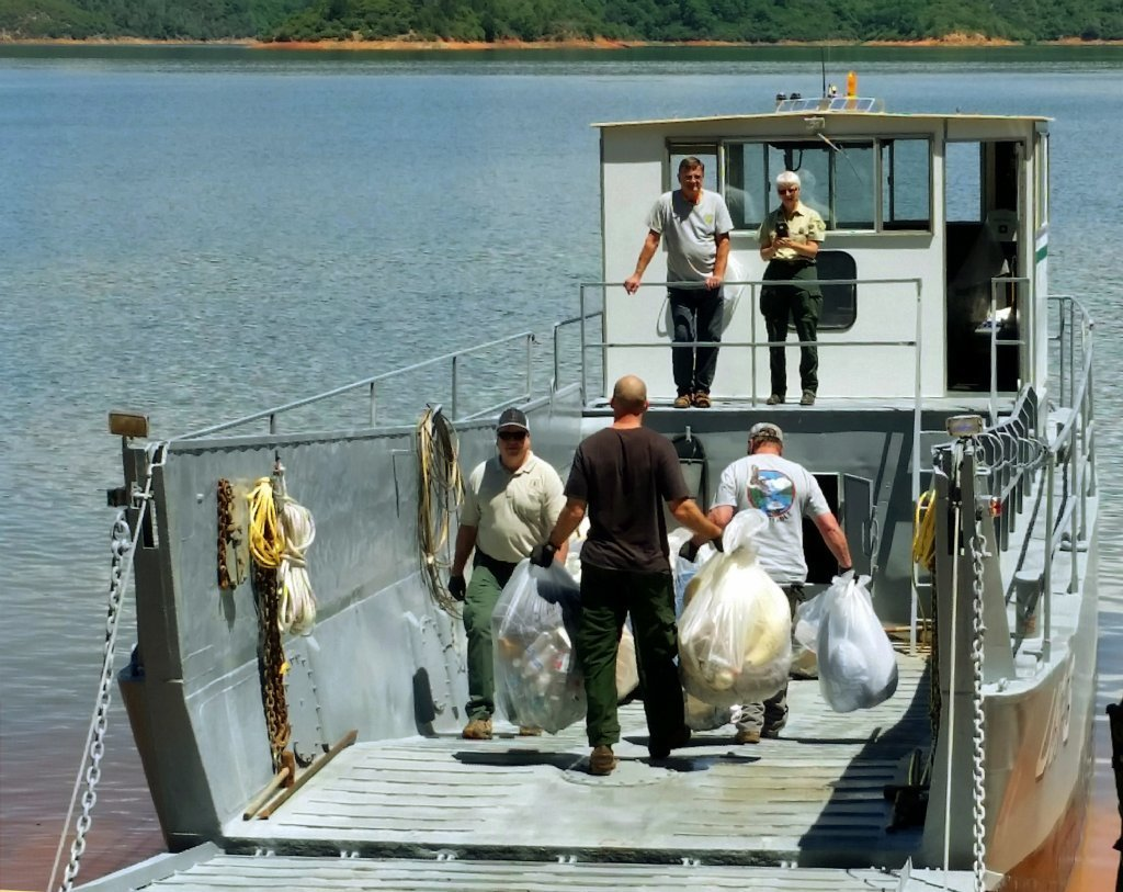 A May 24, 2016, photo provided by the U.S. Forest Service shows workers loading bags of trash onto a boat after cleaning up a half-mile-wide swath of trash left behind by about 1,000 Oregon college campers after an annual trip to Lake Shasta.