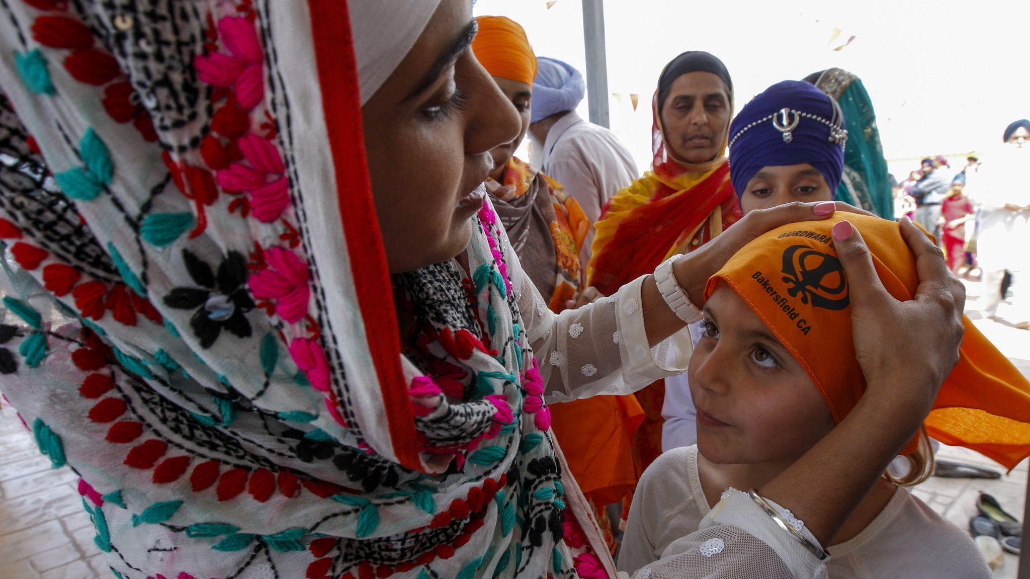 "Sukhpreet ""Sandy"" Kaur, left, helps Emily Villarreal cover her head before entering the gurdwara."