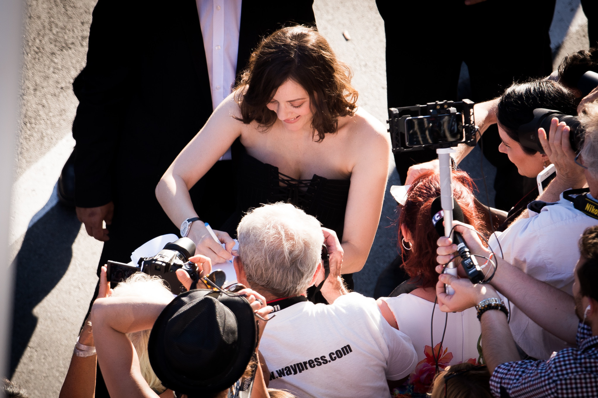 "Marion Cotillard signs an autograph on the red carpet for the opening gala screening of ""Ismael's Ghosts (Les Fantomes d'Ismael)"" at the 70th annual Cannes Film Festival."