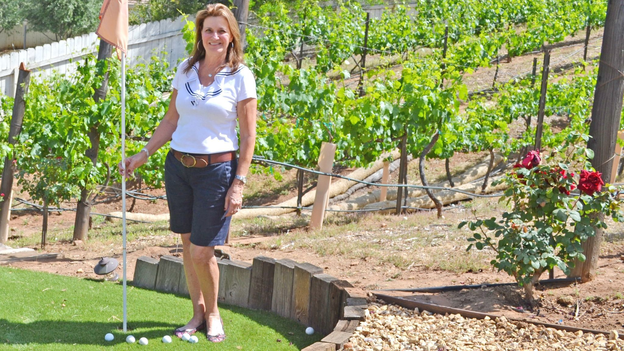 Angela Risotti-Rios stands on one of the three putting greens in their backyard with the vineyard behind her.