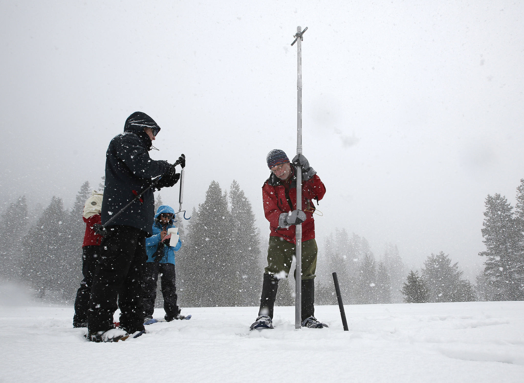Frank Gehrke, right, chief snow surveyor for the Department of Water Resources, lifts his survey tube out of the snowpack at Phillips Station near Echo Summit, Calif.