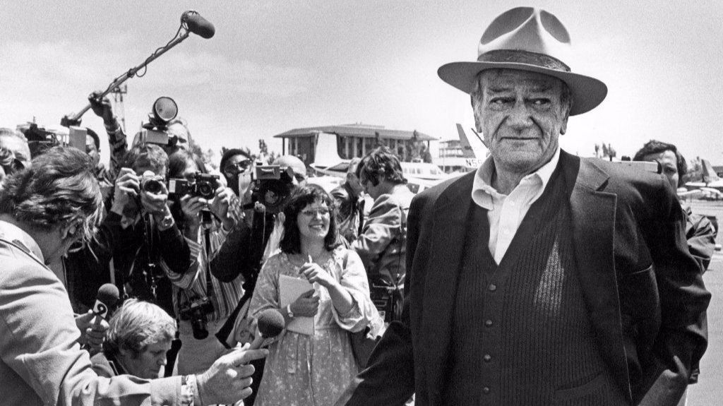 John Wayne chats with newsmen at Orange County Airport in 1978.