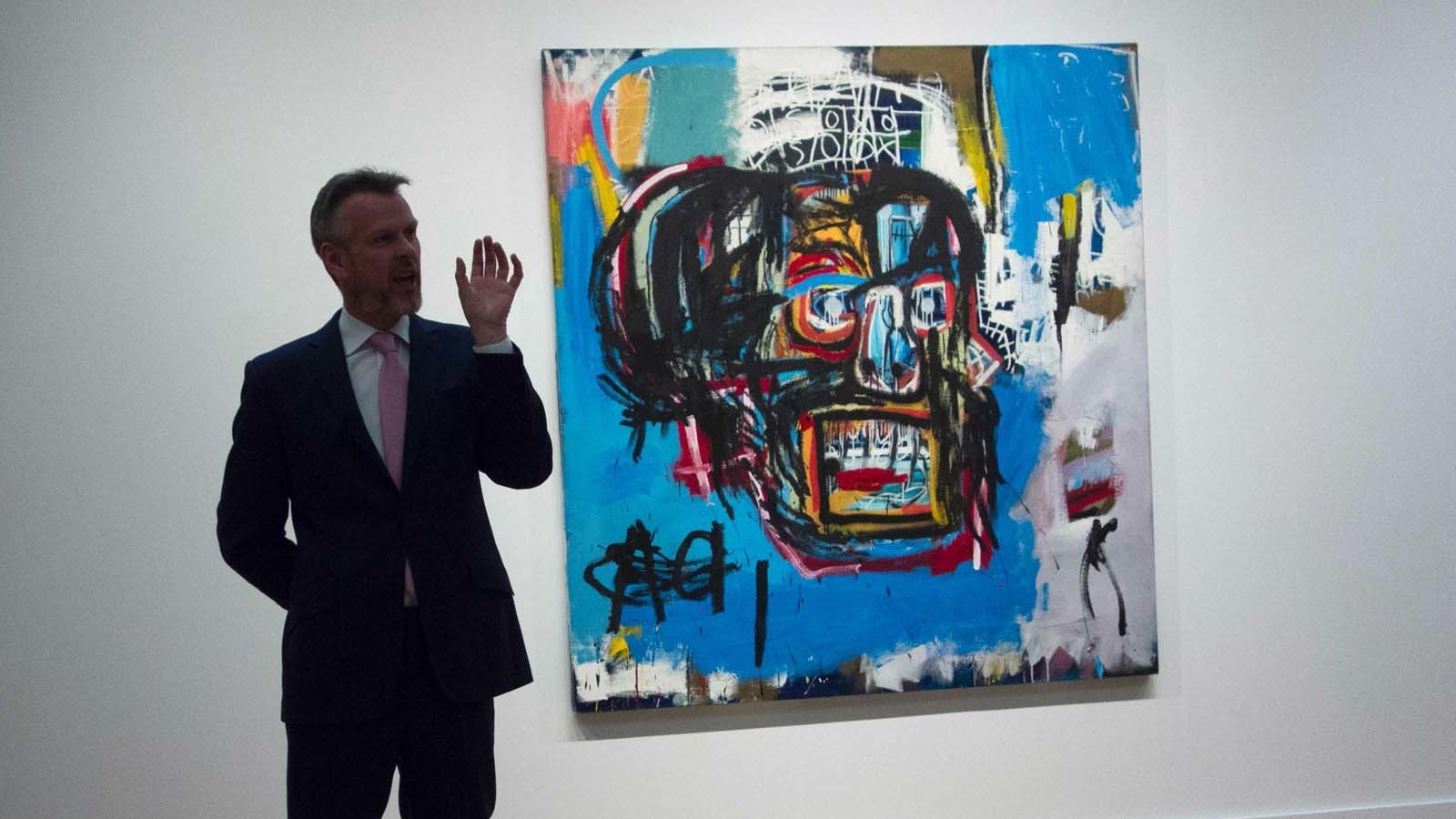 "A Sotheby's official talks about Jean-Michel Basquiat's 1982 ""Untitled"" on May 5, 2017. (Don Emmert / AFP/Getty Images)"