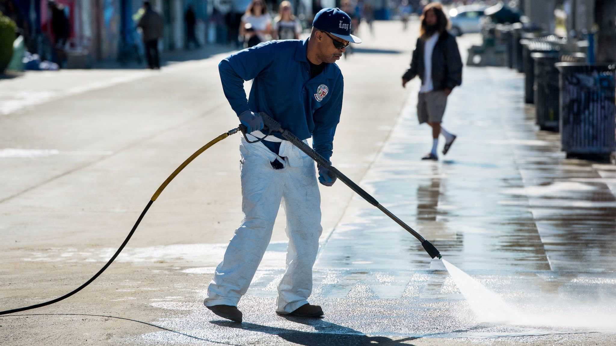 Los Angeles Department of Recreation and Parks employee Ulysses Coleman power washes the Venice Boardwalk. Job growth in Los Angeles county declined last month.