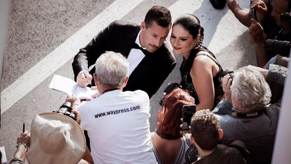 "Adam Sandler does some Cannes multitasking, signing an autograph and posing for a fan photo outside the screening for his new movie ""The Meyerowitz Stories,"" directed by Noah Baumbach."
