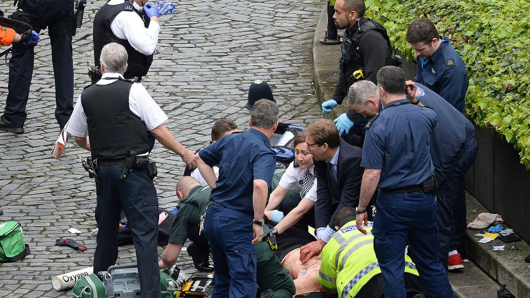 Conservative Member of Parliament Tobias Ellwood, center, helps emergency services attend to an injured person outside the Houses of Parliament in London, England
