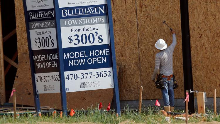 In this Tuesday, May 16, 2017, photo, a construction worker continues work on new town homes under c