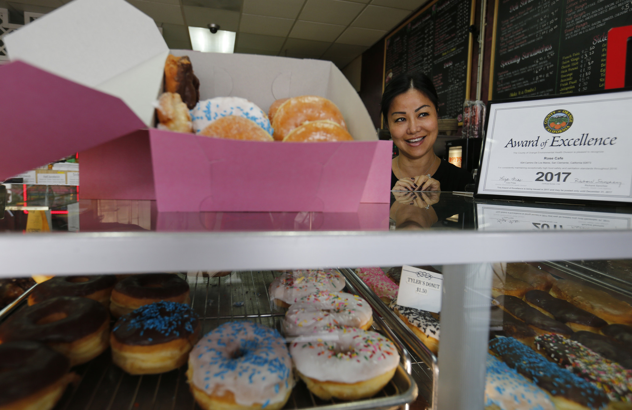 Susan Lim, the Cambodian American owner of Rose Donuts & Cafe, serves doughnuts at her San Clemente store.