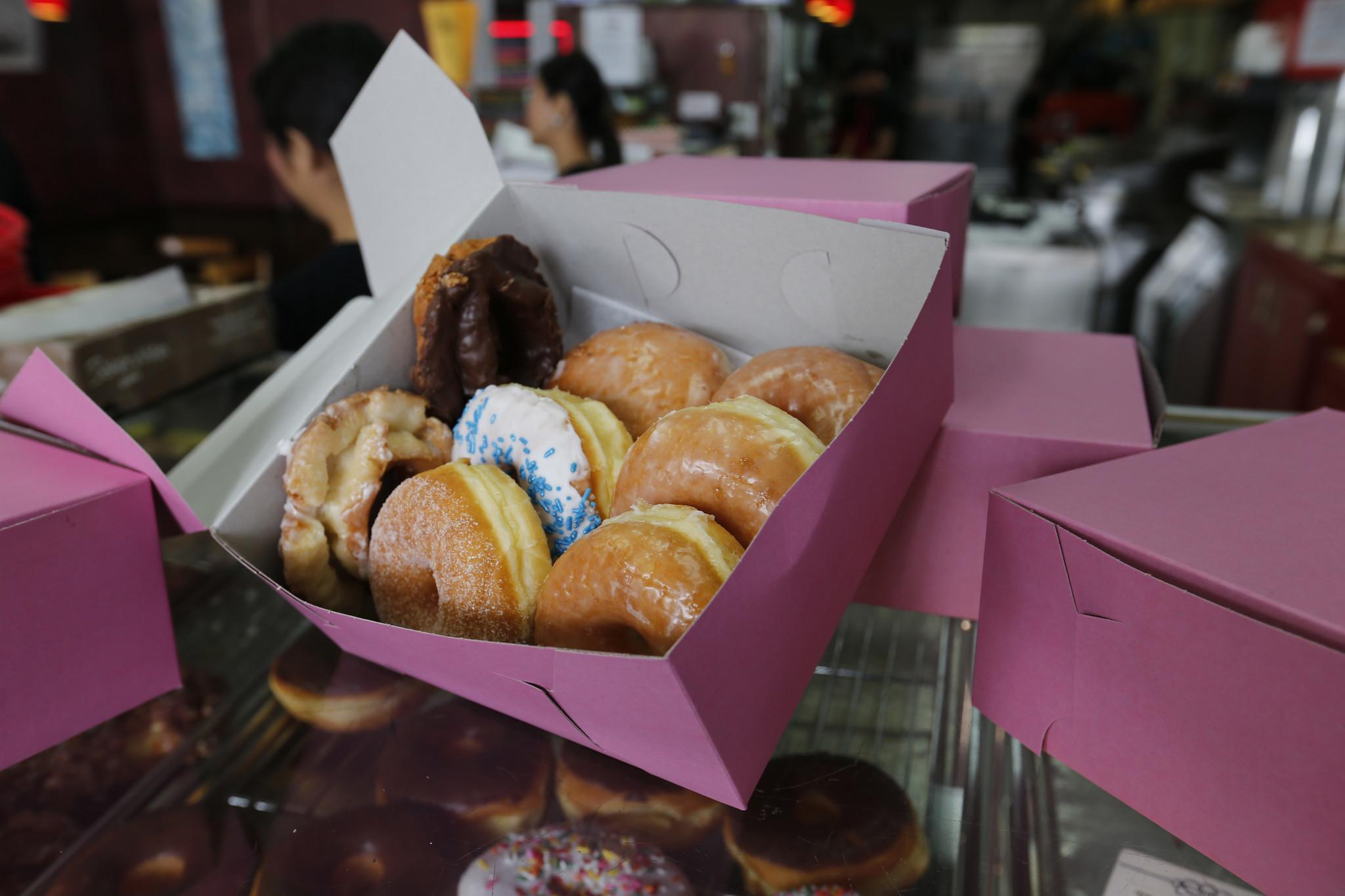 Susan Lim entrega una docena de donas en una caja rosada en su tienda Rose Donuts & Cafe,  en San Clemente.