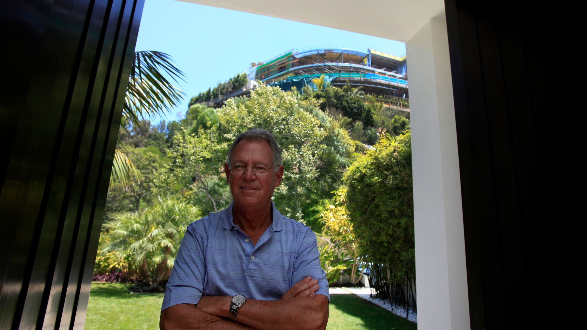 Joseph Horacek stands at the entrance to his Bel-Air home in 2014. Behind him, on the top of the hill, is the unfinished house on Strada Vecchia Road.