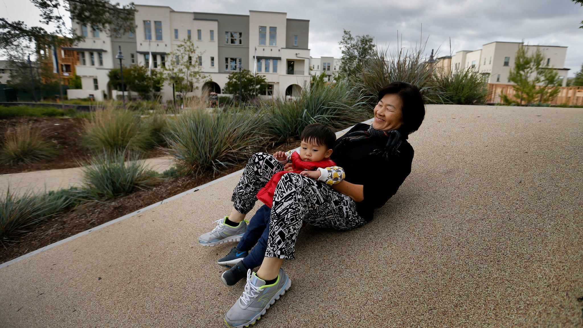 "Doris Han, 60, plays with grandson Aaron at Beacon Park. She treasures their time together in a place she described as having ""so much peace and with lots of not good English speakers, like me."""