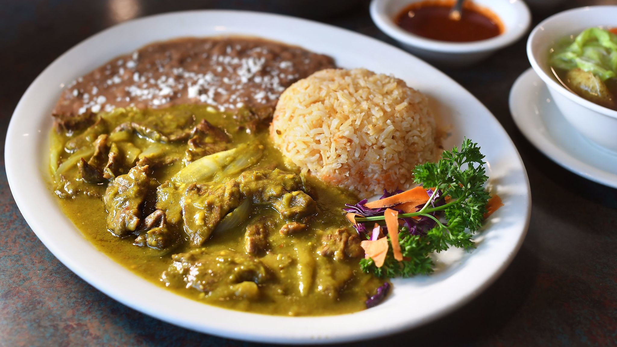Carne de res en chile verde, diced flank steak in a green hot chile sauce, is served with rice and beans at Teresitas Restaurant in Los Angeles.