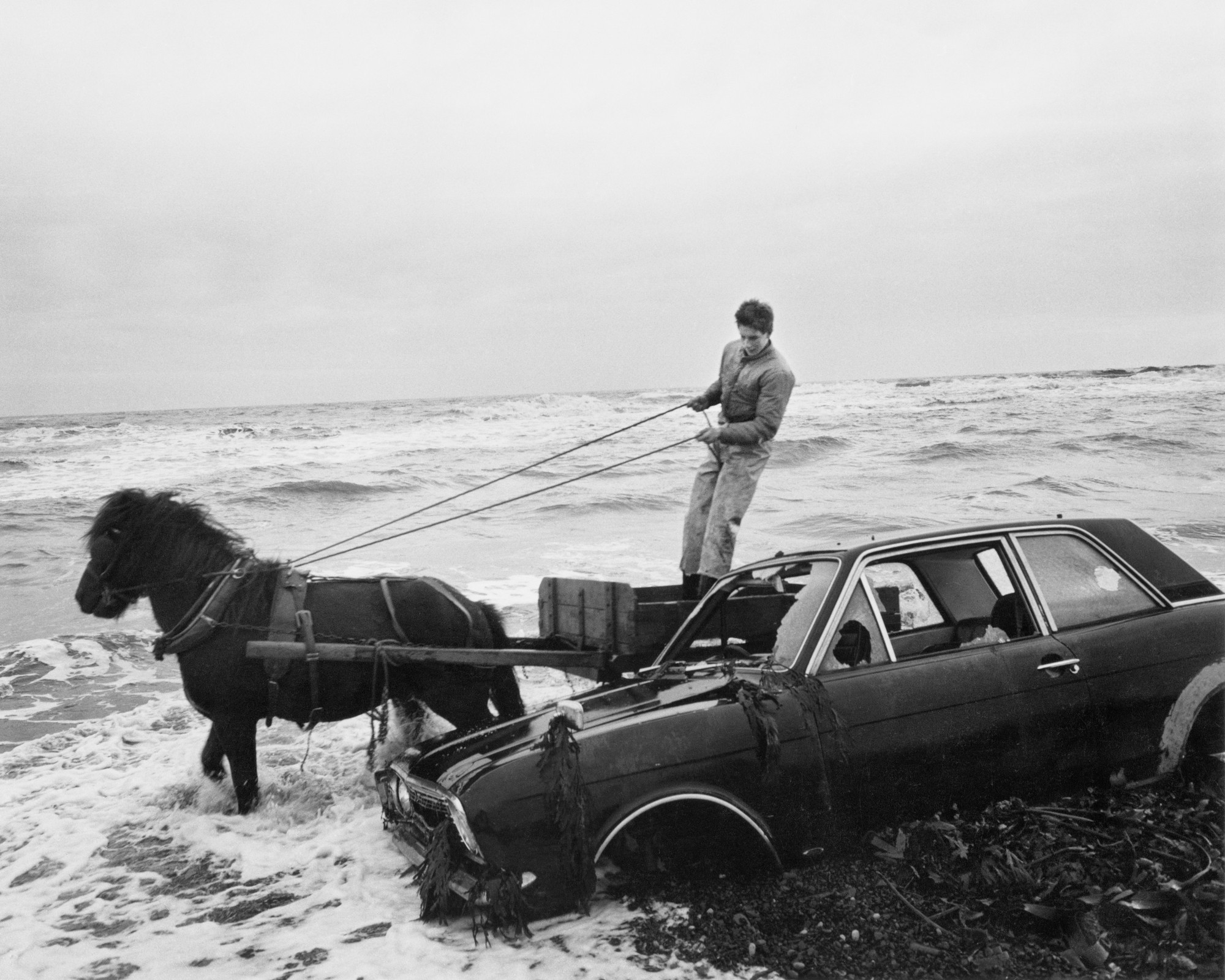 """A car dumped on the beach..."" by Chris Killiip, from 1982, at the Getty Museum."