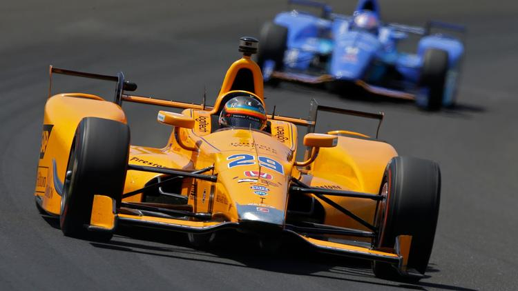 Fernando Alonso leads Scott Dixon through the first turn during practice for the Indianapolis 500 on