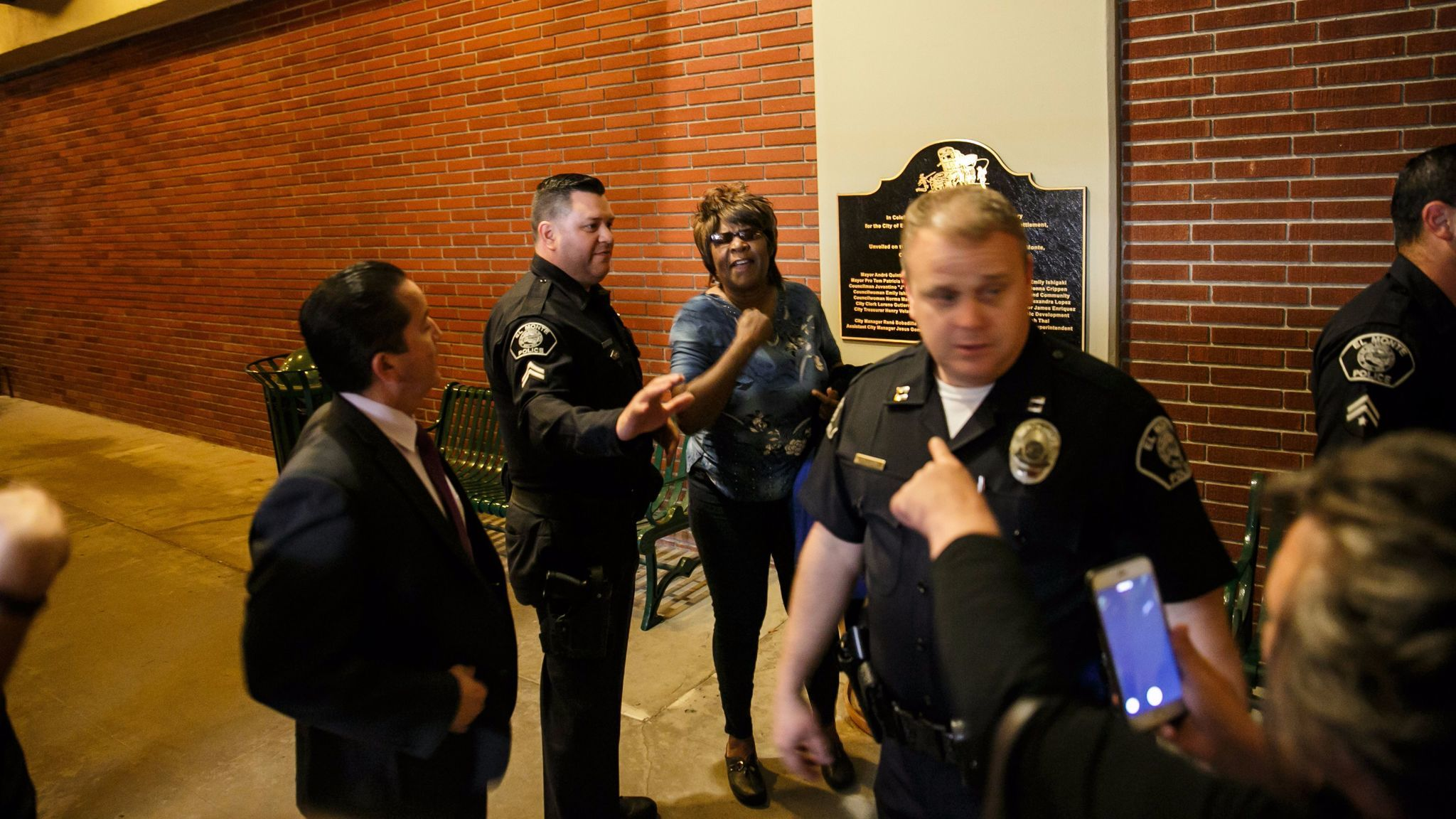 Chanell Temple is pulled aside by police after a brief scuffle broke out outside an El Monte City Council meeting on May 3. Pointing at her is El Monte resident Veronica Tomas, with back to camera.
