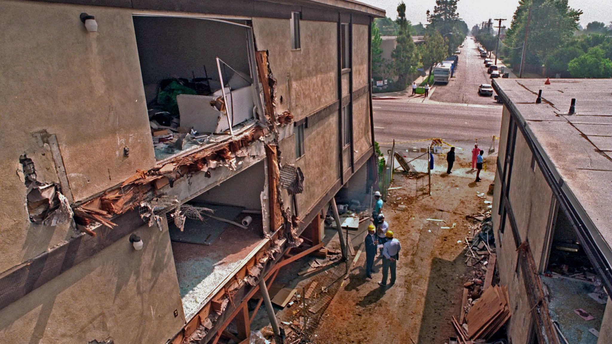 Workers begin to demolish the Northridge Meadows apartment building, whose ground floor collapsed in the 1994 earthquake.