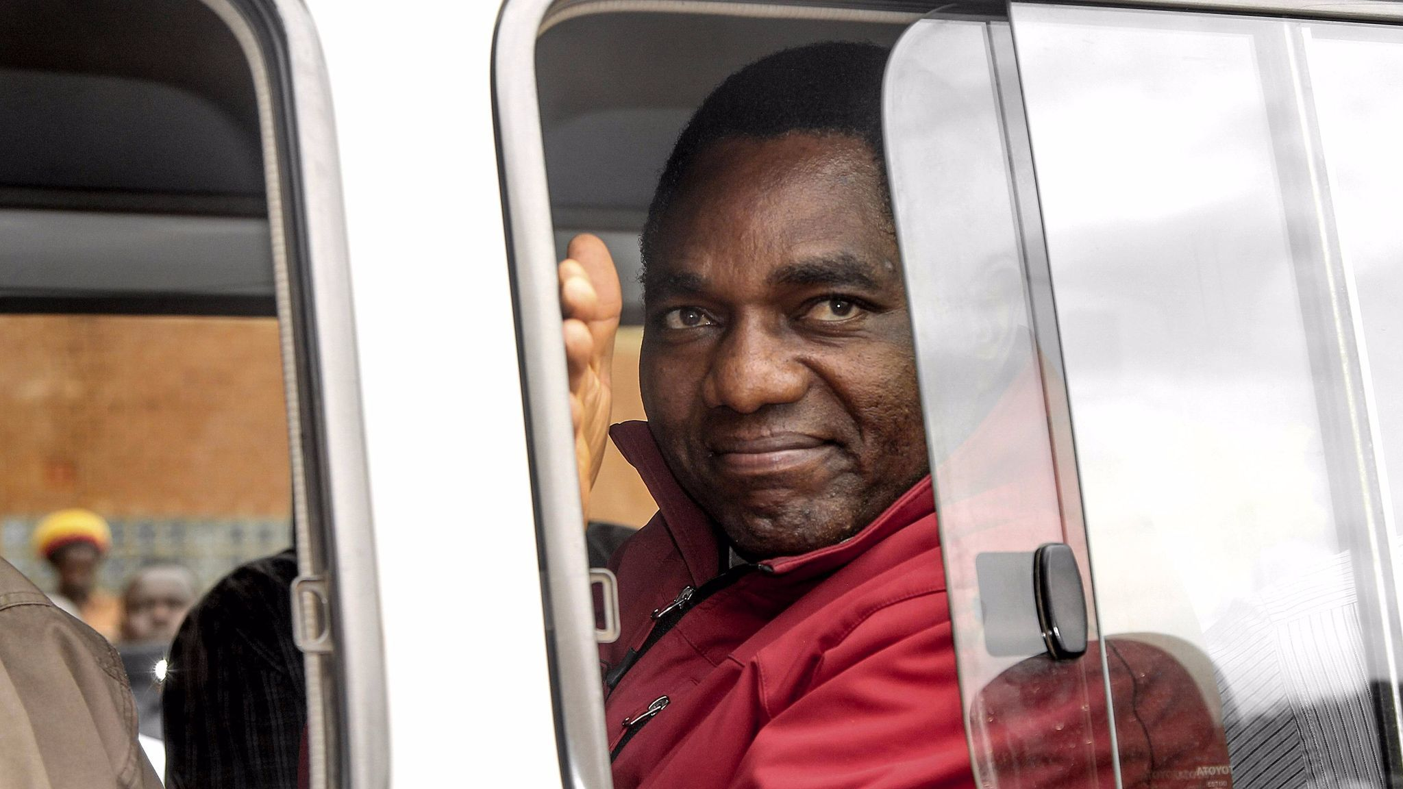 Jailed Zambian opposition leader Hakainde Hichilema, facing treason charges and possibly the death penalty, waves to supporters from a police van as he leaves a court hearing April 18.