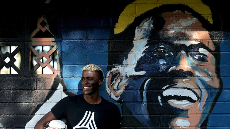 Galaxy forward Gyasi Zardes stands next to a mural of himself at Hawthorne Memorial Park. He grew up