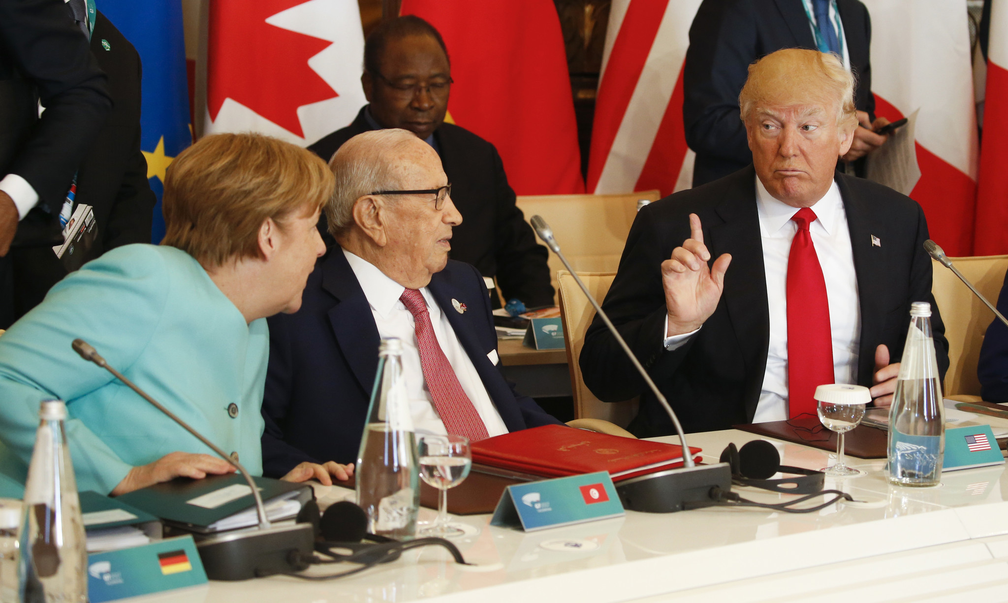 President Trump talks to German Chancellor Angela Merkel and Tunisian President Beji Caid Essebsi at a G-7 summit expanded session in Taormina, Italy, on May 27. (Associated Press)
