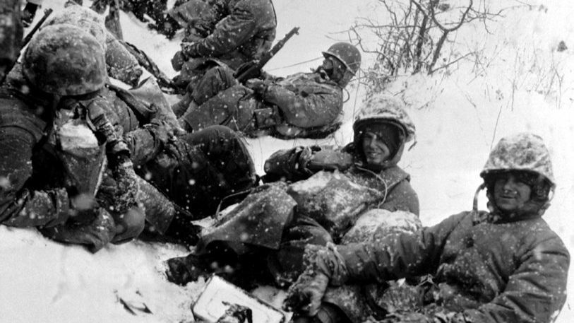 U.S. Marines, fighting their way from the communist encirclement at Chosin to Hungnam, rest in the snow in December 1950, a few months into the Korean War.