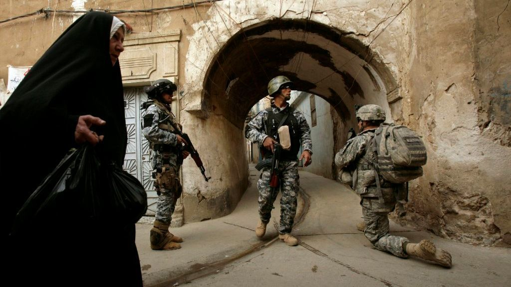 U.S. troops and Iraqi police officers stand guard in Mosul, Iraq, in  2003.