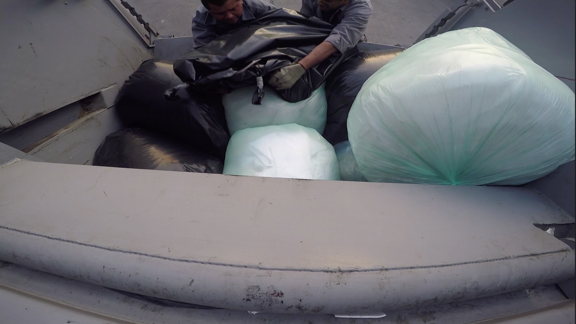 "A video still of sanitation workers loading artist Regina Jose Galindo, in a garbage bag, as part of a performance called ""Desecho."""