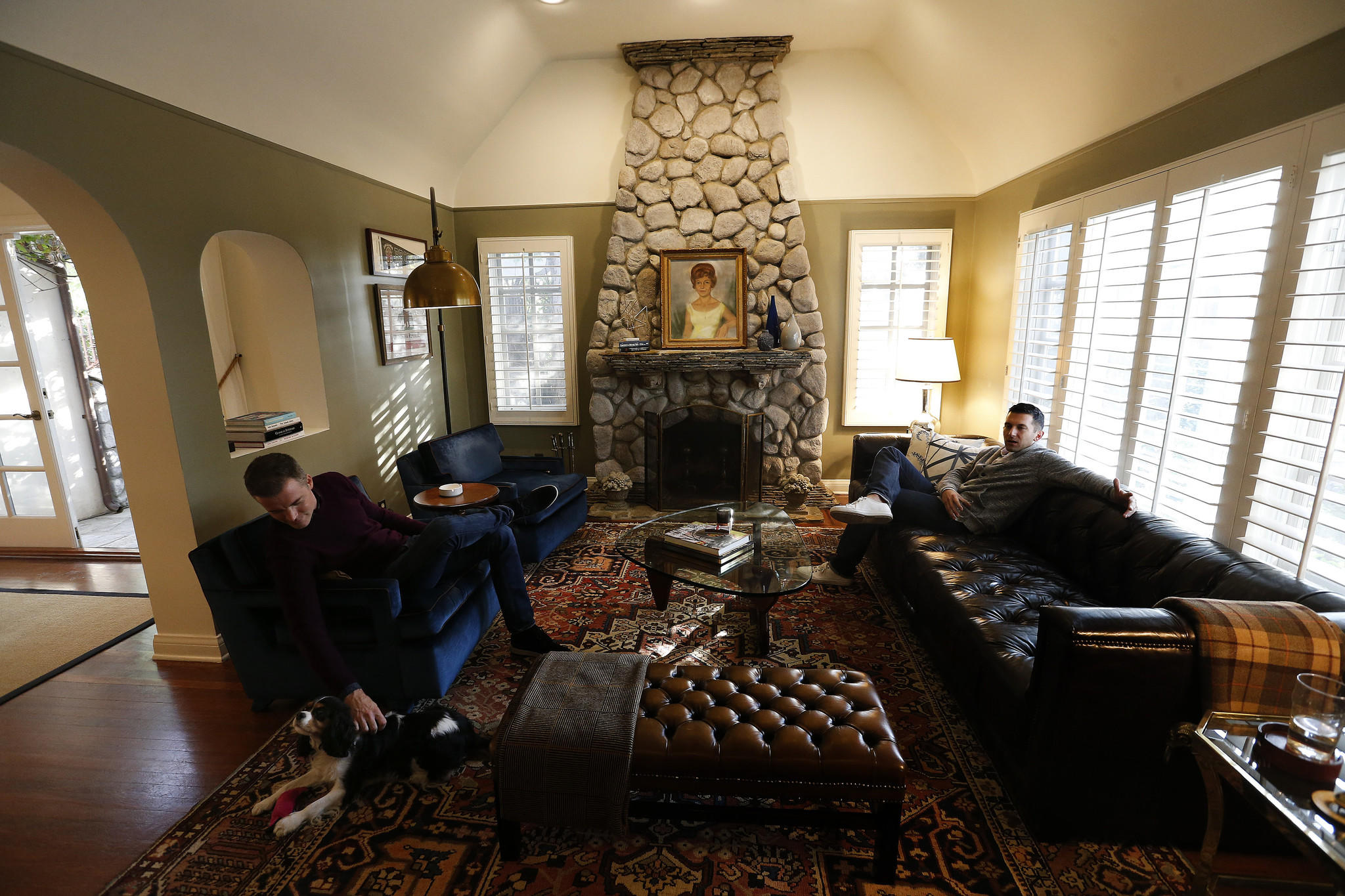 Patrick Wildnauer, left, and his husband Tom Balamaci,  sit inside the living room of their English cottage style home.