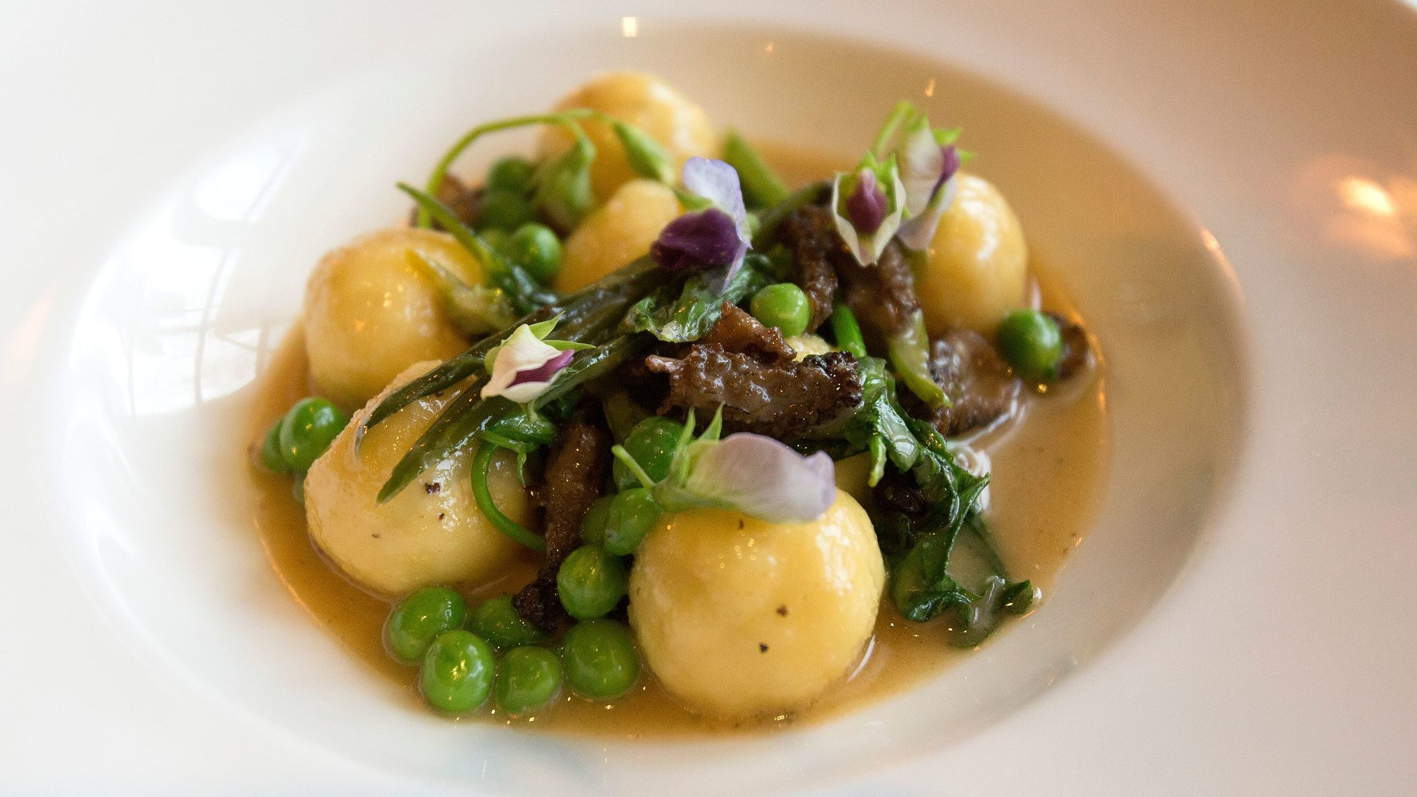 The ricotta gnudi with morels, garlic scapes and English peas at Osteria Mozza.