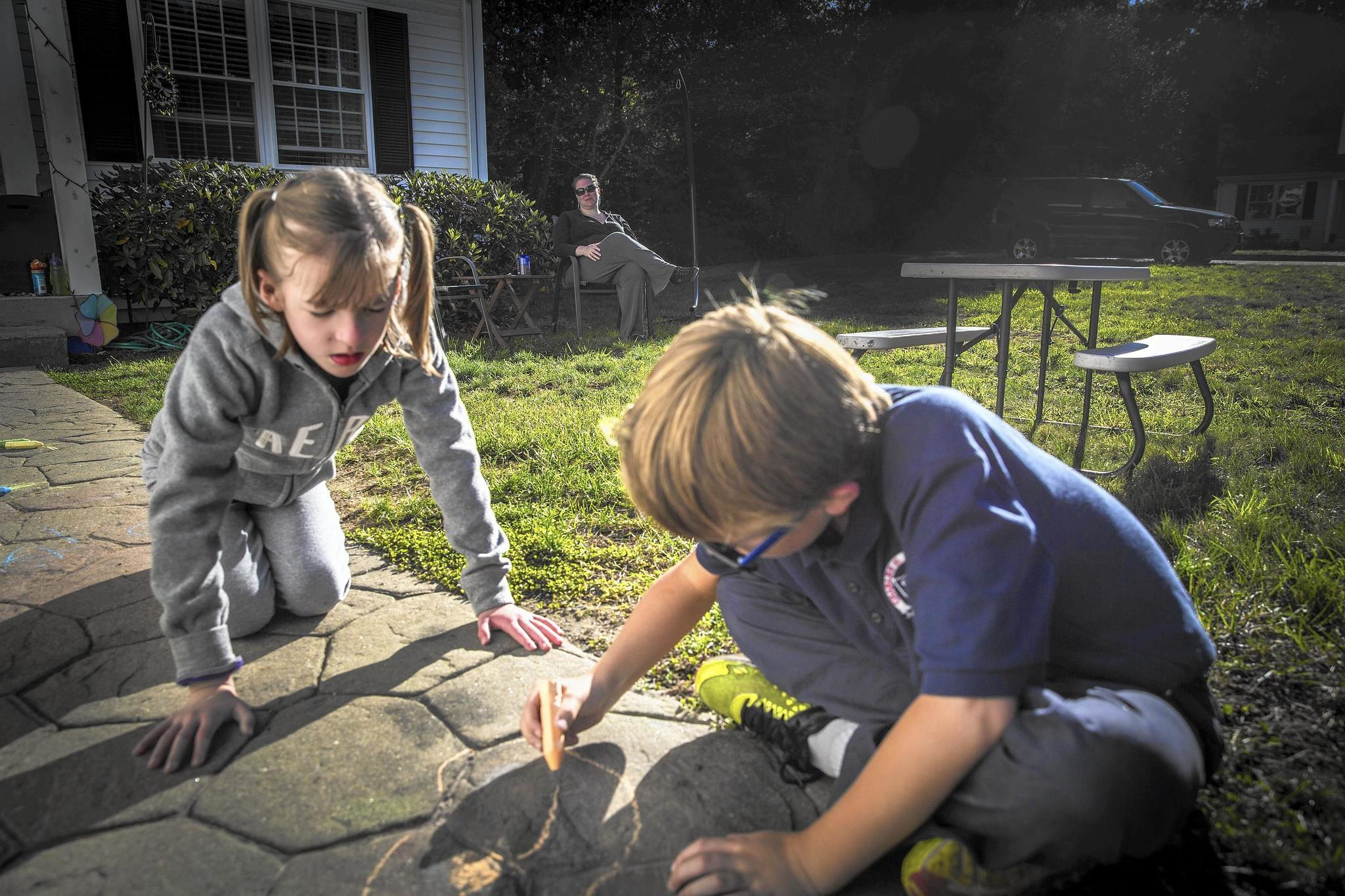 West Tarricone and her brother, Blake play with chalk in front of their house in North Windham while their mom watches in the background on Oct. 11, 2016. The twins are very close, though Blake does not suffer from epilepsy. Blake usually plays with West when he comes home from school. West attends school for a few hours when she is feeling up to it, but on many days her seizures cause her to stay home.
