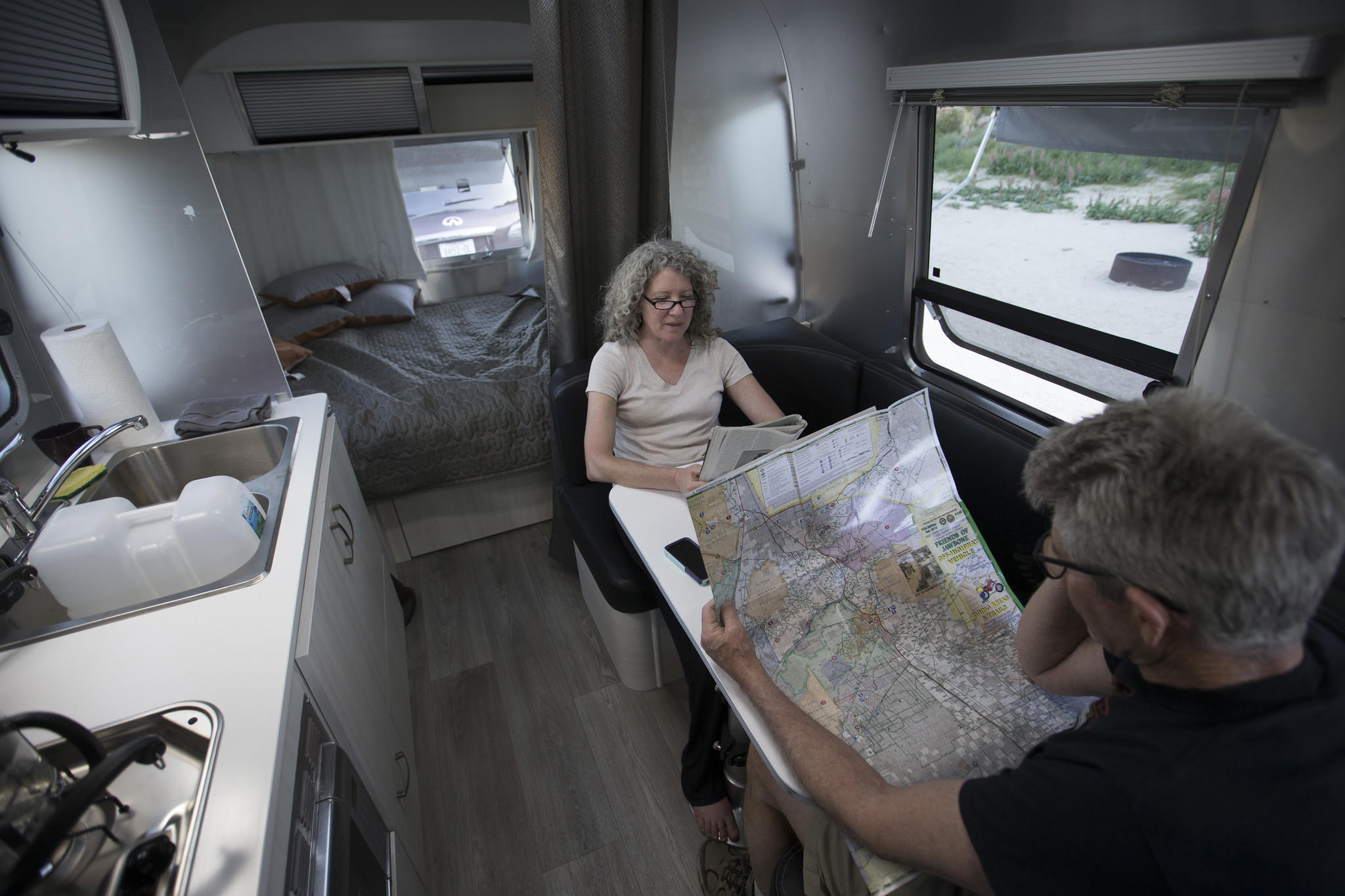 Charles and Julie Fleming check out a map while camping in an Airstream Bambi Sport at Red Rock Canyon Ricardo campground.