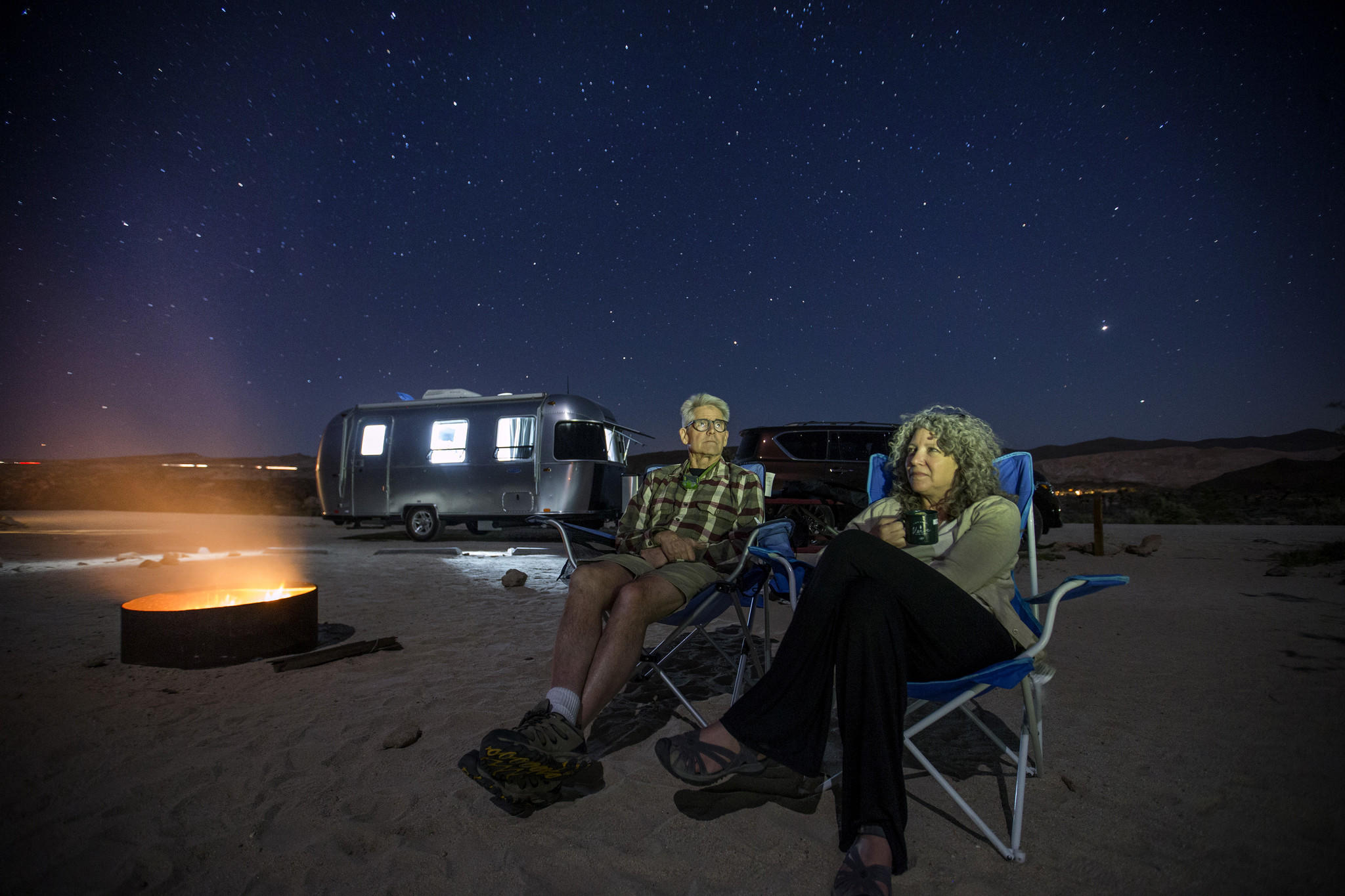 Charles and Julie Fleming check out the stars on a clear night by a campfire at dusk while camping in an Airstream Bambi Sport at Red Rock Canyon Ricardo campground.