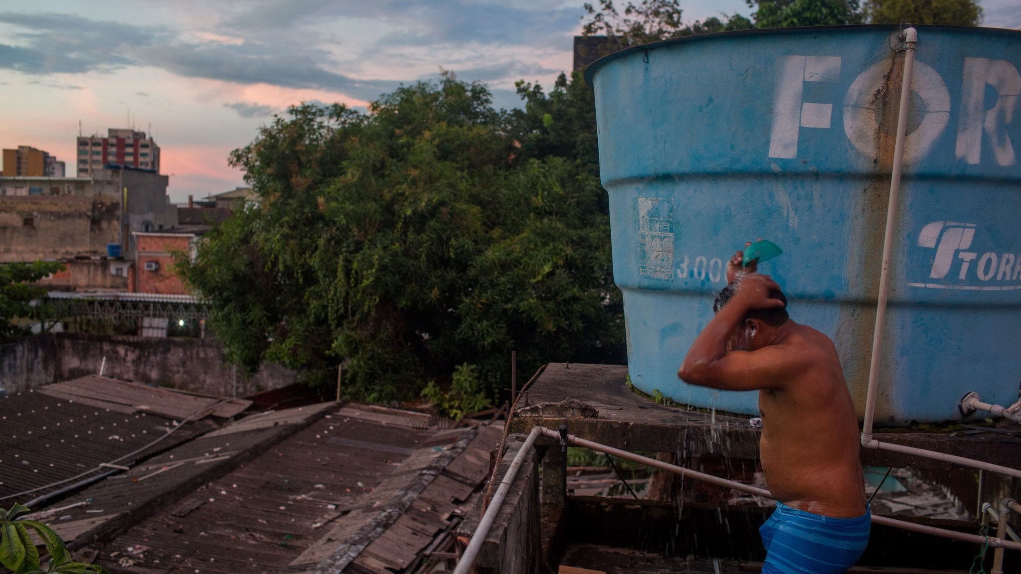 A Warao man bathes on a rooftop in Manaus, Brazil. About 350 Warao Indians live in public squares and old mansions in central Manaus.