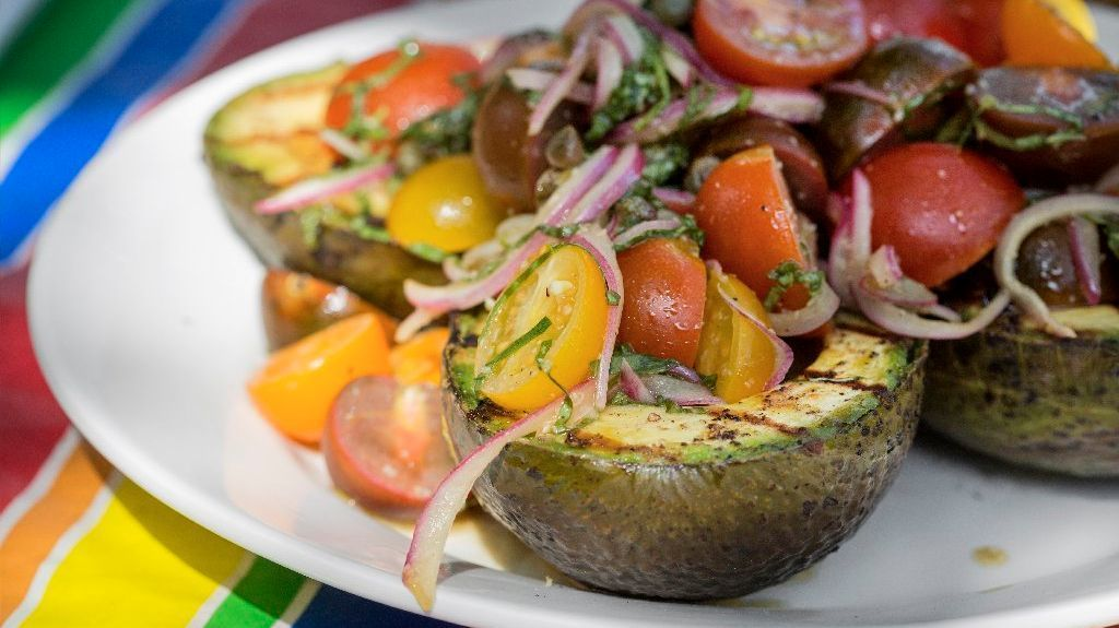 Grilled avocado with marinated tomato salad.