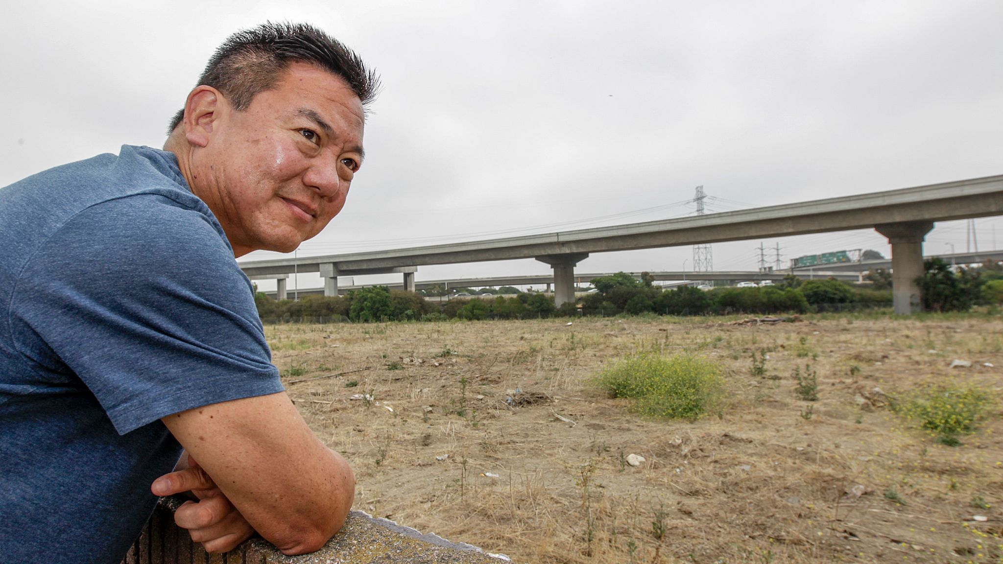 Harbor Gateway resident Craig Kusunoki looks from his backyard wall onto the site of a proposed 15-home subdivision planned near the interchange of the 110 and 91 Freeways. Opponents say future residents will face noise and air pollution from nearby cars and trucks.