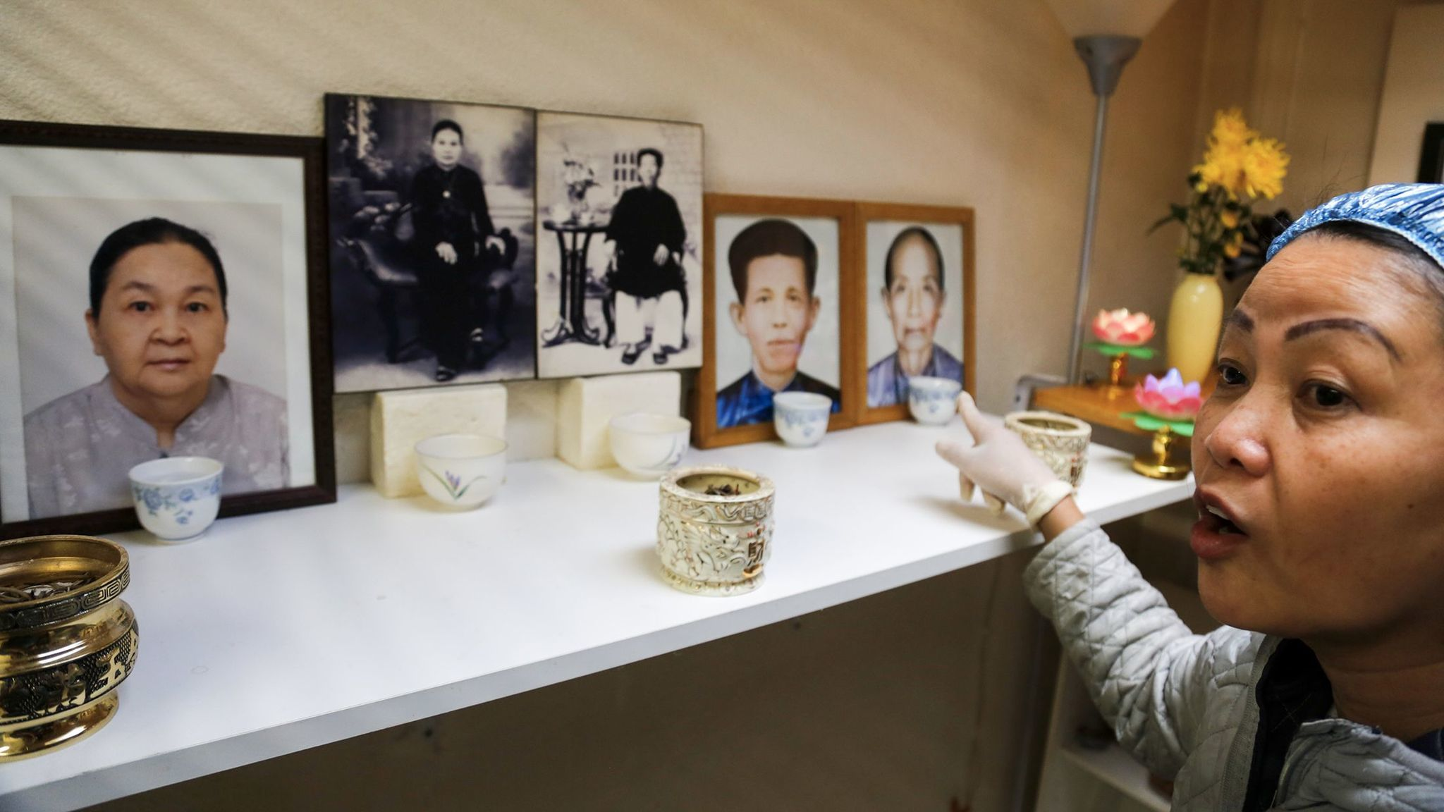 Hue Phan points to pictures of her and her husband's parents and grandparents arranged for a home shrine.