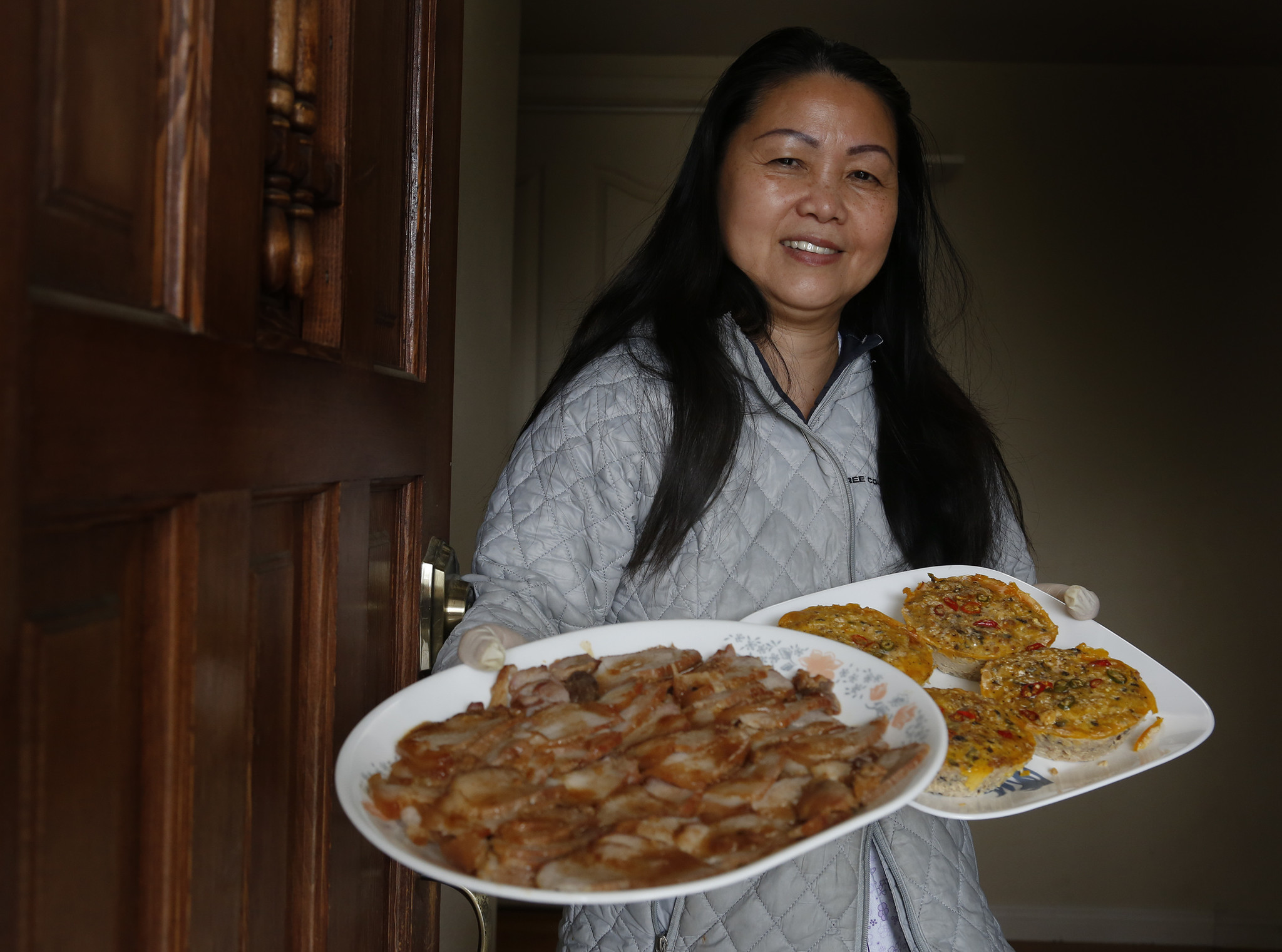 "After several hours of hard work, Hue Phan displays some of the finished dishes of barbecue pork and ""mam chung"" that she will package for delivery."