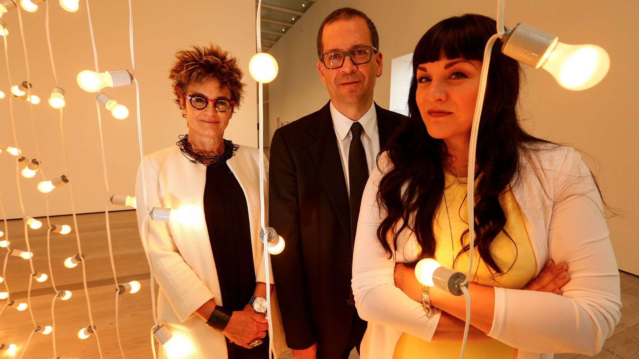 Curators Mari Carmen Ramirez, Chon A. Noriega and Pilar Tompkins Rivas stand next to a work by the late Felix Gonzalez-Torres at LACMA.