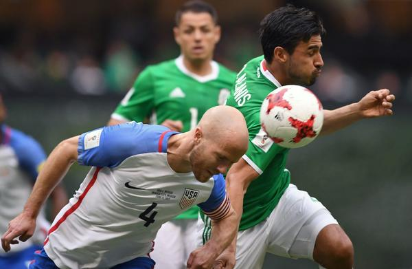 U.S. midfielder Michael Bradley tries to head the ball away from Mexico's Oswaldo Alanis. (Alfredo Estrella / AFP / Getty Images)