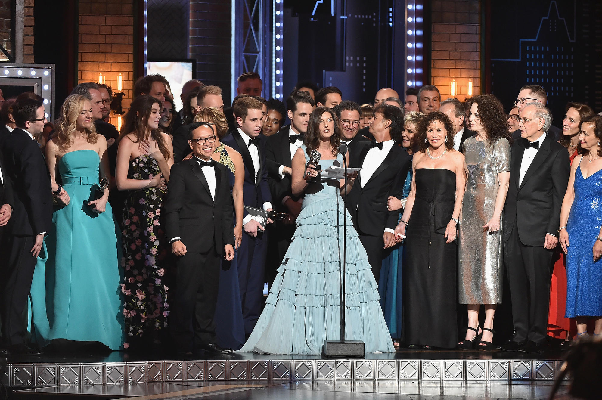 "Producer Stacey Mindich, at the microphone, and the cast of ""Dear Evan Hansen"" accept the award for"