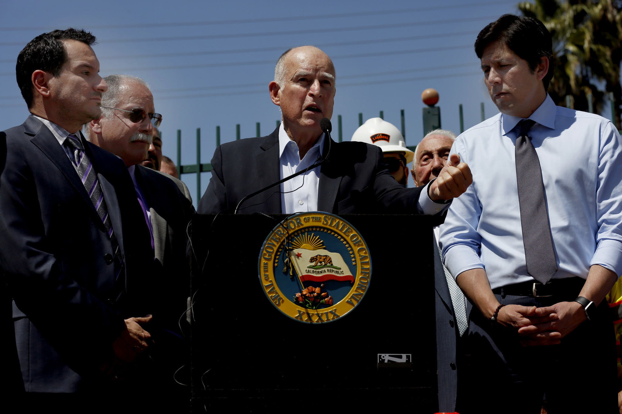 Assembly Speaker Anthony Rendon, left, Gov. Jerry Brown and Senate President Pro Tem Kevin de León appear in Riverside in April to call for gas tax hike. All three are getting raises. (Francine Orr / Los Angeles Times)