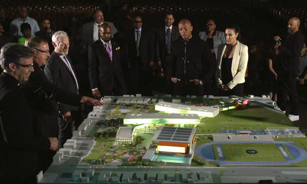 Dr. Dre, center, with hands in pockets, views a model of the performing arts complex he is helping to fund as part of the new Compton High School. (Compton Unified School District)